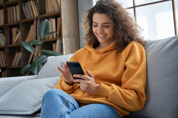 Woman smiling while looking at her phone