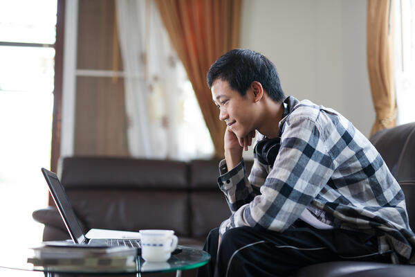 Boy smiling while looking at his laptop